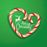 Christmas Frame in candy canes heart shape on green background. Stock Photos