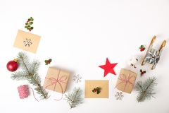 Christmas frame composition. Christmas gift,pine branch, red balls, envelope, white wood snowflakes, ribbon and red berries. Top v. Iew, flat lay, copy space Royalty Free Stock Photo