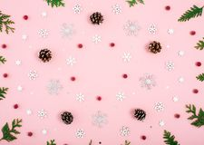 Christmas frame composition. Pattern with snowflakes, cones, red berries and tree branches on pastel pink background. Flat lay stock photography