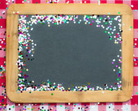 Christmas frame of confetti on blackboard Royalty Free Stock Image