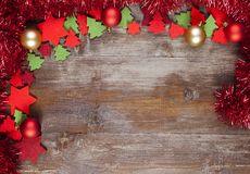 A Christmas Frame decorated with garlands, christmas balls and d. A Christmas Frame decorated with red garland, red and golden christmas balls and red stras of Stock Photography
