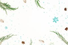 Christmas frame of evergreen tree branches, blue snowflakes and pine cone on white background. Flat lay, top view. Winter concept. Christmas frame of evergreen stock photo