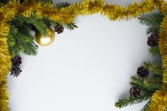 Christmas frame. Festive decorations such as gold tinsel and baubles, conifer tree branches and cones. Copy space for wishes. stock photo