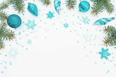 Christmas frame of fir branch, blue decoration and snowflake on white background. Holiday frame. Flat lay, top view. Christmas frame of fir branch, blue stock images