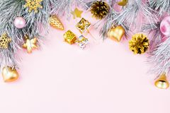 Christmas frame with fir branches, conifer cones, christmas balls and golden ornaments on pastel pink background. Copy space stock photography