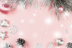 Christmas frame with fir branches, conifer cones, christmas balls and silver ornaments on pastel pink background. Copy space royalty free stock image