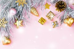 Christmas frame with fir branches, conifer cones, christmas ornaments on pastel pink background with snow falling Stock Photos