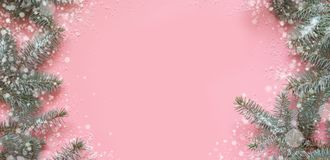 Christmas frame of fir branches, snowy white decorations on pink table. Xmas background. Flat lay. Top view with copy space. Christmas frame made of fir branches stock photo