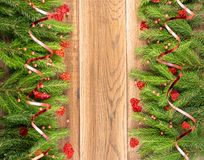 Christmas frame with fir branches on wooden background. Christmas background with fir branches on wooden backdrop flat lay and top view. Yuletide floral frame royalty free stock images