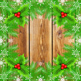 Christmas frame with fir and holly berry. On wooden background Stock Photography