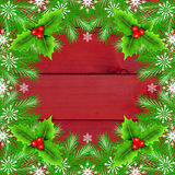 Christmas frame with fir tree. Branches and holly berry on wooden background Royalty Free Stock Photo