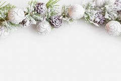 Christmas frame with fir tree branches with snow, balls ornament. S and cones with copy space, festive greeting, top view royalty free stock images