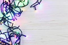 Christmas frame of garland lights. colorful stylish border on wh Stock Image