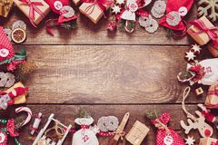 Christmas frame with gifts, candy and handicrafts. Christmas frame with colorful red themed gifts, decorations, candy and handicrafts on vintage rustic wood royalty free stock photos