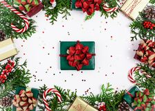 Christmas frame with gifts, tree branches, candy cane, cones and star confetti. View from the top stock photography