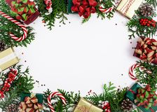 Christmas frame with gifts, tree branches, candy cane, cones and star confetti. View from the top. Copy space royalty free stock photos