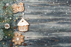 Christmas Frame of Gingerbread cookies on spruce over snowy wooden background copy space royalty free stock photo