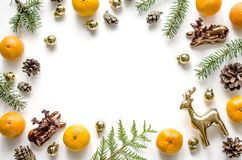 Christmas frame with golden deers, mandarins, fir branches and New Year balls and cones on a white background. Royalty Free Stock Photo