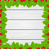Christmas frame of holly berries on wooden background Stock Image