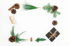 Christmas frame made of black gift box, branches of winter trees and pine cones on white background. Flat lay. Top view Royalty Free Stock Photo