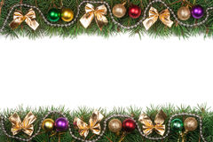 Christmas frame made of fir branches decorated with balls beads and golden bows isolated on white background. Christmas frame made of fir branches decorated with Stock Images