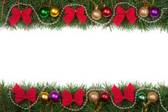 Christmas frame made of fir branches decorated with balls beads and red bows isolated on white background. Christmas frame made of fir branches decorated with Royalty Free Stock Photo