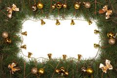 Christmas frame made of fir branches decorated with balls bells and bows isolated on white background.  Royalty Free Stock Image