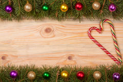 Christmas frame made of fir branches decorated with balls and candy cane on a light wooden background Royalty Free Stock Images
