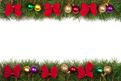 Christmas frame made of fir branches decorated with balls and red bows isolated on white background. Christmas frame made of fir branches decorated with balls Stock Photo