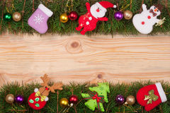 Christmas frame made of fir branches decorated with balls Snowman and Santa Claus on a light wooden background Royalty Free Stock Photo
