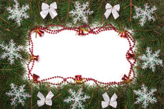 Christmas frame made of fir branches decorated with bows bells and snowflakes isolated on white background Royalty Free Stock Image