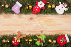 Christmas frame made of fir branches decorated with golden balls Snowman and Santa Claus on a light wooden background Stock Photo