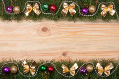 Christmas frame made of fir branches decorated with golden bows beads and balls on a light wooden background Stock Image