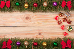 Christmas frame made of fir branches decorated with red bows and balls on a light wooden background Royalty Free Stock Image