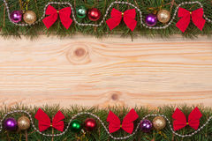 Christmas frame made of fir branches decorated with red bows beads and balls on a light wooden background.  Royalty Free Stock Photo
