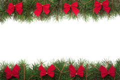Christmas frame made of fir branches decorated with red bows isolated on white background Stock Images