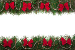 Christmas frame made of fir branches decorated with red bows isolated on white background.  Royalty Free Stock Photos