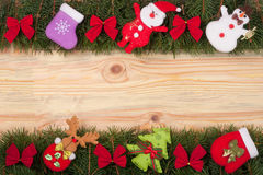 Christmas frame made of fir branches decorated with red bows Snowman and Santa Claus on a light wooden background Stock Image