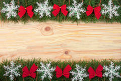 Christmas frame made of fir branches decorated with snowflakes and red bows on a light wooden background royalty free stock photography