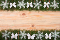 Christmas frame made of fir branches decorated with snowflakes and white bows on a light wooden background Stock Photos