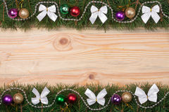 Christmas frame made of fir branches decorated with white bows beads and balls on a light wooden background.  Royalty Free Stock Photo