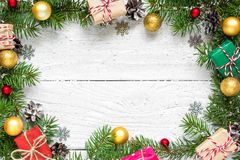 Christmas frame made of fir branches, red and golden decorations, gift boxes and pine cones. On white wooden table. Christmas background. Flat lay. top view Royalty Free Stock Photo