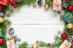 Christmas frame made of fir branches, red and golden decorations, gift boxes and pine cones. On white wooden table. Christmas background. Flat lay. top view Stock Images