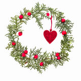 Christmas frame made of green thuja twigs, red wild rose fruits and Xmas tree decoration felt heart on white background Stock Photography