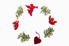 Christmas frame made of green thuja twigs, rowan berries and xmas tree decorations on white background. Top view, flat Stock Photography
