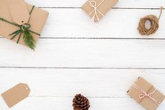 Christmas frame made of present gifts box with decoration rustic elements on white wooden. Christmas background. Christmas frame made of present gifts box with Royalty Free Stock Photo