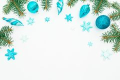 Christmas frame made of winter trees, blue decoration and snowflake on white background. Holiday frame. Flat lay, top view Stock Photos
