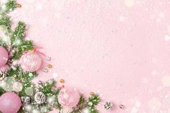 Christmas frame of New Year ornaments and snow on pink background. Christmas frame of New Year ornaments, fir and snow on pastel pink. Winter holidays, New Year stock images