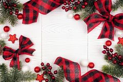 Free Christmas Frame Of Ornaments, Branches And Red And Black Checked Buffalo Plaid Ribbon, Top View On A White Wood Background Royalty Free Stock Images - 163688249