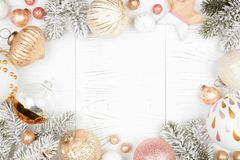Free Christmas Frame Of Snowy Branches And Dusty Rose, Gold, And White Ornaments On A White Wood Background Stock Image - 162992501